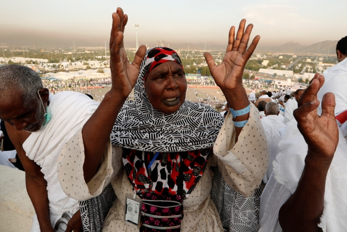 A Muslim pilgrim prays as she gathers with others on Mount Mercy on the plains of Arafat during the annual haj pilgrimage, outside the holy city of Mecca